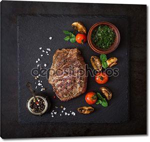 Сочный стейк с пряностями и овощами гриль.