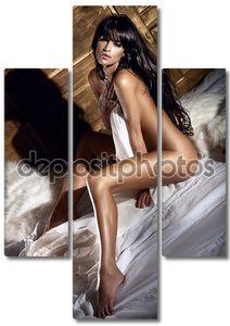 Красивая голая брюнетка женщина сидит на большой кровати и позирует