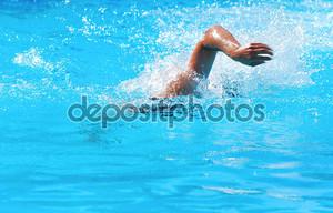 Молодой человек, плавание в бассейне передней обхода