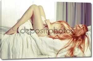 Чувственная женщина с красными волосами в постели