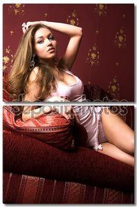 Красивая девушка на красном диване.