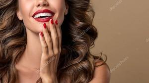 Красивая смеющаяся брюнетка модель девушка с длинными вьющимися волосами. Улыбающаяся женщина с волнистыми кудрями. Красные губы и ногти маникюр. Мода, красота и макияж