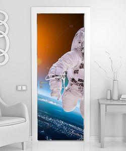 Космонавт в открытом космосе на фоне солнца