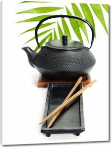 Черный чайник рядом с палочками