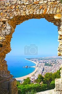 вид испанский пляж через каменная дверь замок Святого Иоанна курортный городок Бланес в летнее время. Коста Брава, Каталония, Испания