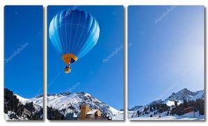 Воздушный шар пролетел выше горного хребта на ясное голубое небо