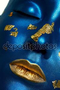 Женская модель с синей кожейи золотыми губами.