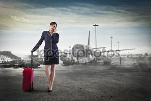 Молодой предприниматель в аэропорту, держа случае тележки и говорить на мобильном телефоне