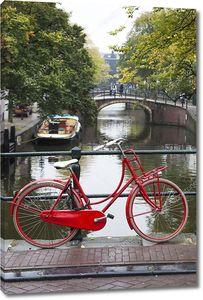 Красный велосипед на мосту в Амстердаме