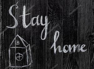 Рисунок с мелом на черной доске, дом и текст остаться дома. Концепция защиты от вирусов