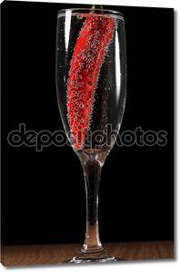 Красный перец, упал в бокал шампанского с пузырьками