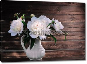 White peonies in a vase on a wooden background