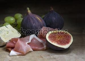 Инжир с ветчиной и сыром на деревенском древесины, продовольствия Натюрморт