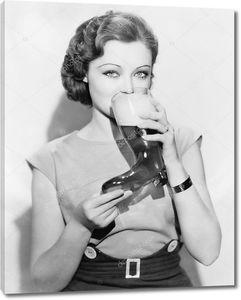 Женщина пьет пиво из бокала в виде сапога