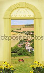 вид через арочные двери, холмистый ландшафт и маленькой деревне