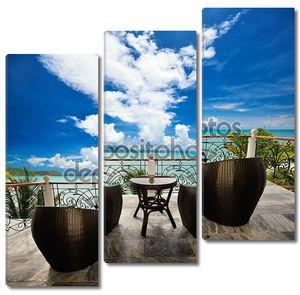 лаунж терраса с креслами из ротанга и видом на море.