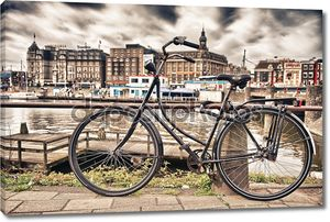 Amsterdam, Netherlands. Colourful bike over a bridge and city channels.