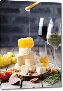 Бокалы вина рядом с сыром и медом