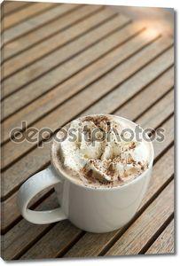 чашка горячего положения во главе шоколада со взбитыми сливками и какао powde
