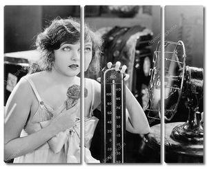 Молодая женщина с огромным термометром ест мороженое