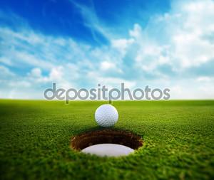 мяч для гольфа около отверстия