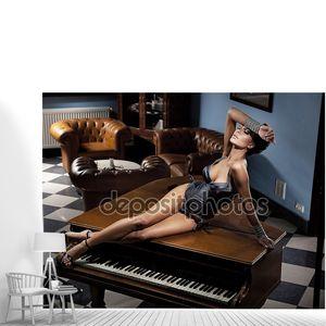 Молодая сексуальная женщина, лежа на фортепиано
