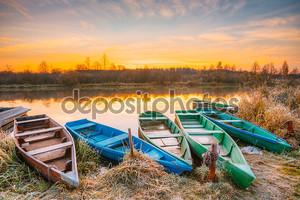 River and old rowing fishing boats at beautiful sunrise sunset