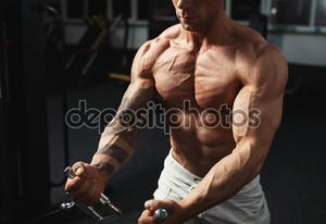 сильный культурист, делая упражнения в тренажерном зале