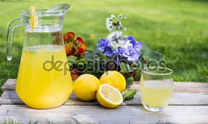 Лимонад в кувшин и лимонов на таблице Открытый