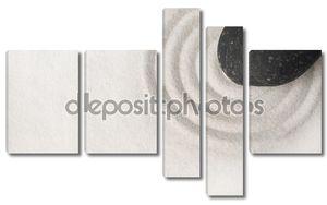 Черный камень на белом песке
