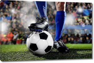 ноги и ноги футболиста в синих носках и черных туфлях, стоящих с мячом, играющим на футбольном стадионе