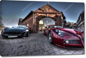 2 Спортивных автомобилей на стоянке паркованных вне здания