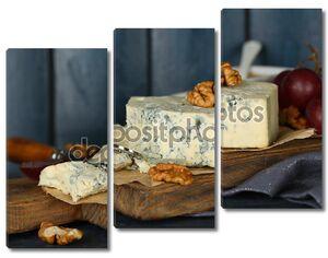 натюрморт со вкусным сыром с плесенью на столе, на деревянном фоне