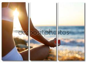 Тело красивой девушки в медитации на пляже