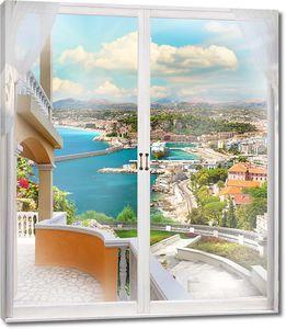Вид из окна на солнечный город и море