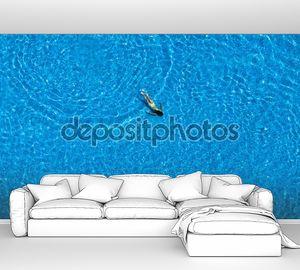 Женщина плавает в бассейне. Вид сверху.