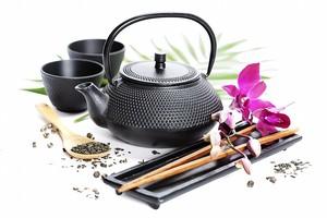 Чайный набор рядом с цветком