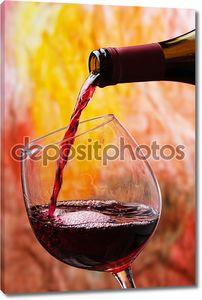 Красное вино наполняет бокал
