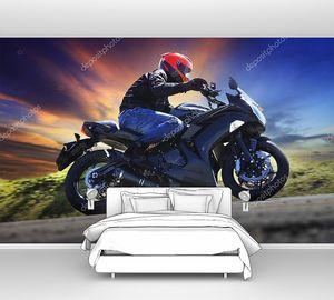 Молодой человек на мотоцикле на дороге