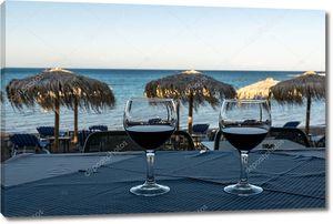 два бокала красного вина на столе на закате на пляже