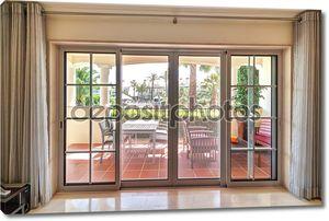 Окна номера с видом на террасу и зеленые сады.