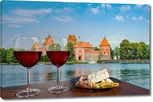 Два бокала красного вина с сыром и мясными закусками с видом на Тракайский замок