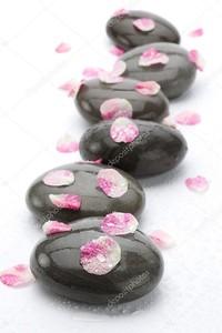 Спа камни с лепестками роз на белом фоне.
