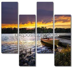 лодка, закрепленной на озеро на закате