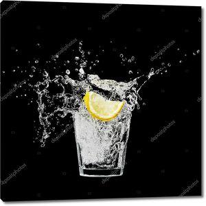 Всплеск в стакан с лимоном и льда на черном фоне