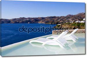 две белые стулья в бассейне с видом на море в Греции