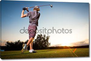 Мужской гольфист teeing от гольф мяч от тройника коробки на красивый закат