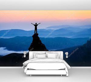 Человек на вершине горы смотрит на солнце