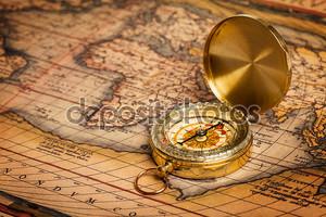 Старый Золотой компас на древней карте