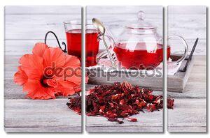 чай из гибискуса в стеклянном чайнике и цветок на цветной салфетки на деревянном фоне